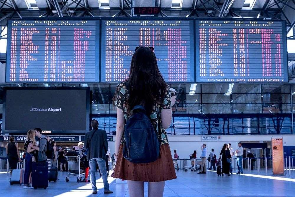 Voyageur devant des tableaux dans un aéroport avec des vols annulés et retardés