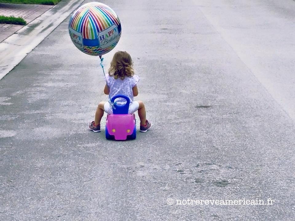 Petite fille sur voiture en plastique